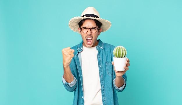 Junger hispanischer mann, der aggressiv mit einem wütenden ausdruck schreit und einen kaktus hält