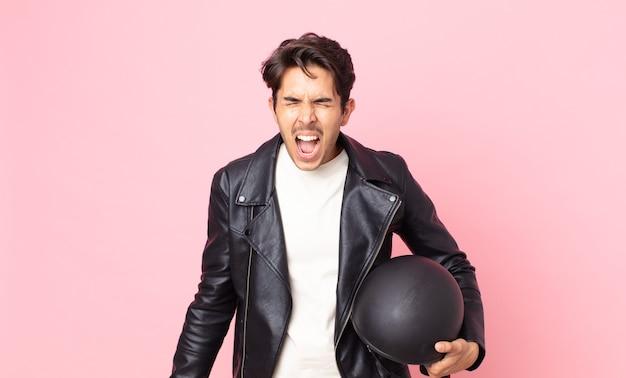 Junger hispanischer mann, der aggressiv schreit und sehr wütend aussieht. motorradfahrerkonzept