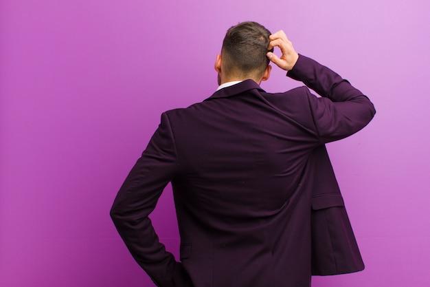 Junger hispanischer mann, der ahnungslos und verwirrt sich fühlt und eine lösung, mit der hand auf hüfte und anderer auf kopf, hintere ansicht denkt