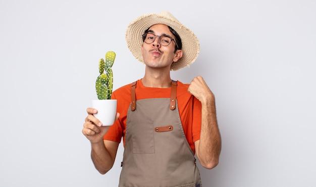 Junger hispanischer mann, der arrogant, erfolgreich, positiv und stolz aussieht. gärtner mit kaktus-konzept