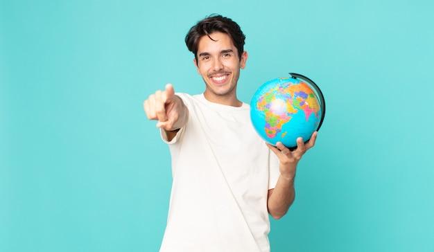 Junger hispanischer mann, der auf die kamera zeigt, die sie auswählt und eine weltkugelkarte hält