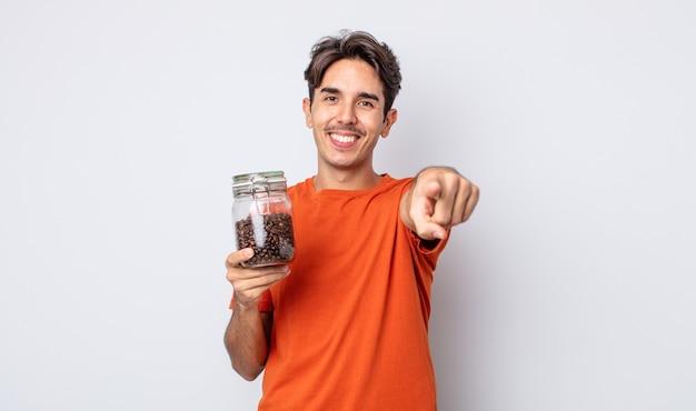 Junger hispanischer mann, der auf die kamera zeigt, die sie wählt. kaffeebohnen-konzept