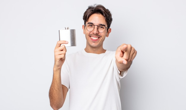 Junger hispanischer mann, der auf die kamera zeigt, die sie wählt. konzept der alkoholflasche