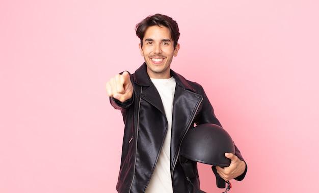 Junger hispanischer mann, der auf die kamera zeigt, die sie wählt. motorradfahrerkonzept
