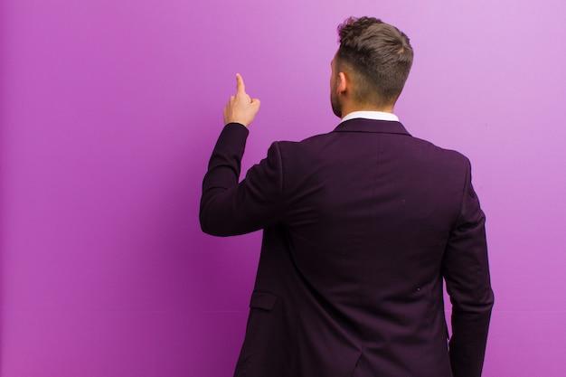 Junger hispanischer mann, der auf gegenstand auf kopienraum, hintere ansicht steht und zeigt