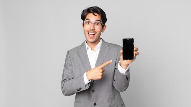 Junger hispanischer mann, der aufgeregt und überrascht aussieht, der auf die seite zeigt und ein smartphone hält