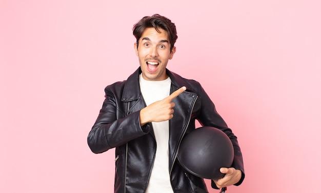 Junger hispanischer mann, der aufgeregt und überrascht aussieht und auf die seite zeigt. motorradfahrerkonzept