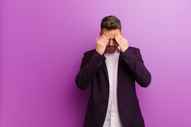 Junger hispanischer mann, der betont und frustriert schaut, unter druck mit kopfschmerzen arbeitet und mit problemen beunruhigt ist