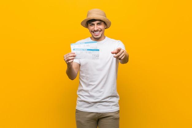 Junger hispanischer mann, der das freundliche lächeln der flugtickets zeigt auf front hält.