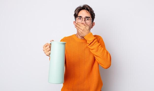 Junger hispanischer mann, der den mund mit den händen mit einem schockierten bedeckt. thermos-konzept