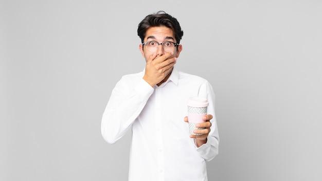 Junger hispanischer mann, der den mund mit den händen mit einem schockierten bedeckt und einen kaffee zum mitnehmen hält