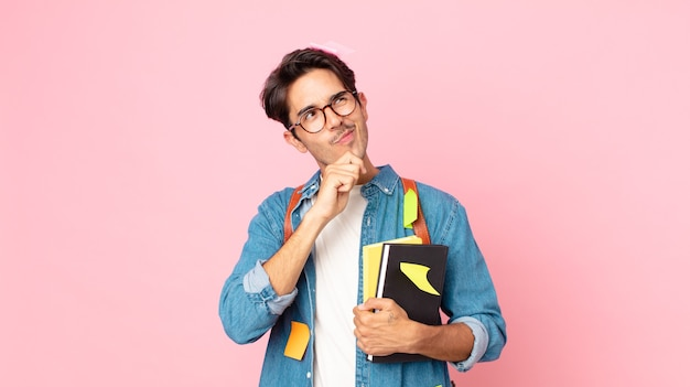 Junger hispanischer mann, der denkt, sich zweifelhaft und verwirrt fühlt. studentisches konzept