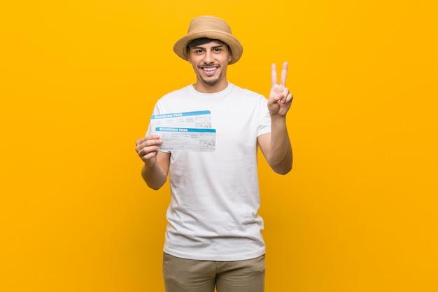 Junger hispanischer mann, der die flugtickets halten, die nummer zwei mit den fingern zeigen.