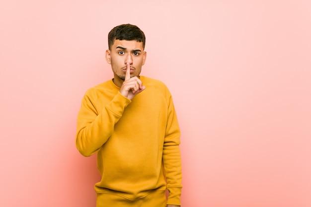 Junger hispanischer mann, der ein geheimnis hält oder um ruhe bittet.