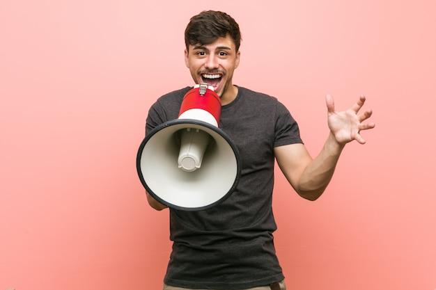 Junger hispanischer mann, der ein megaphon feiert einen sieg hält