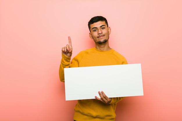 Junger hispanischer mann, der ein plakat hält