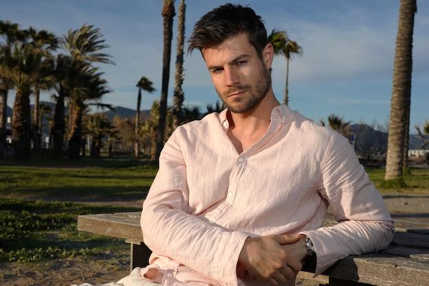 Junger hispanischer mann, der ein rosa hemd trägt und am strand in der nähe von palmen posiert