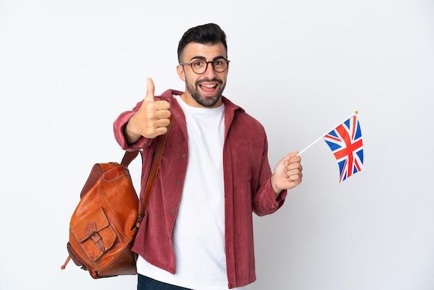 Junger hispanischer mann, der eine britische flagge mit erhobenem daumen hält, weil etwas gutes passiert ist