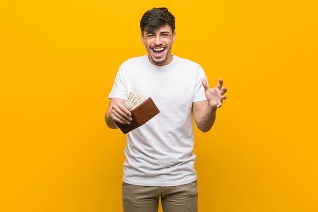 Junger hispanischer mann, der eine geldbörse feiert einen sieg oder einen erfolg hält