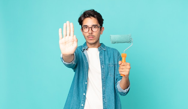Junger hispanischer mann, der ernst aussieht und eine offene handfläche zeigt, die stopp-geste macht und einen farbroller hält