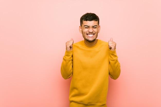 Junger hispanischer mann, der faust anhebt, glücklich und erfolgreich sich fühlt. sieg.