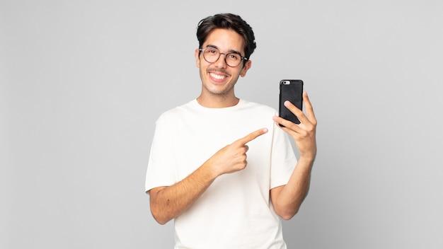 Junger hispanischer mann, der fröhlich lächelt, sich glücklich fühlt und auf die seite zeigt und ein smartphone hält