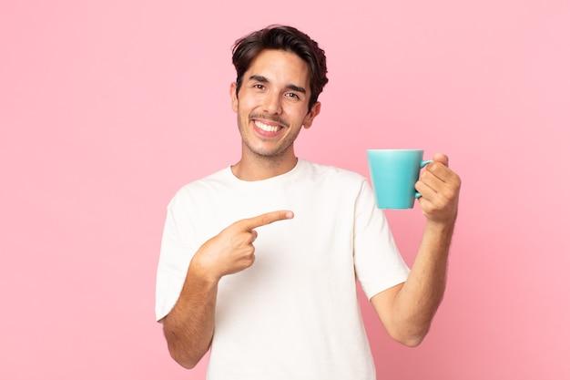 Junger hispanischer mann, der fröhlich lächelt, sich glücklich fühlt und auf die seite zeigt und eine kaffeetasse hält