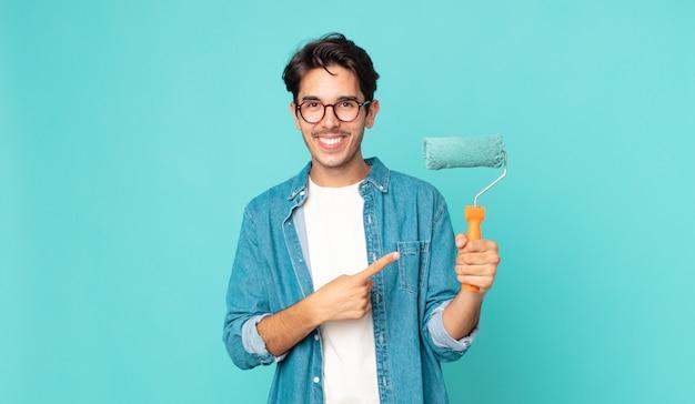 Junger hispanischer mann, der fröhlich lächelt, sich glücklich fühlt und auf die seite zeigt und einen farbroller hält