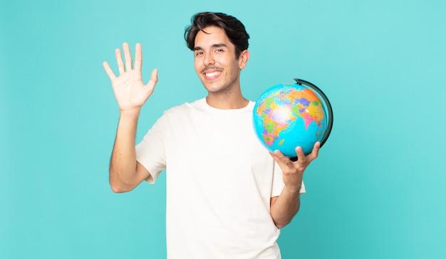 Junger hispanischer mann, der glücklich lächelt, die hand winkt, sie begrüßt und begrüßt und eine weltkugelkarte hält
