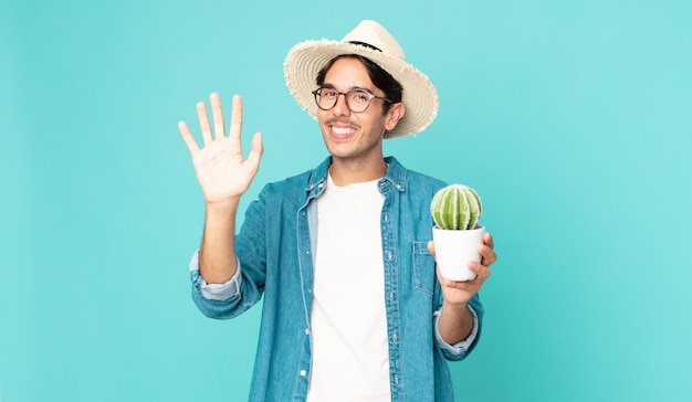 Junger hispanischer mann, der glücklich lächelt, die hand winkt, sie begrüßt und begrüßt und einen kaktus hält