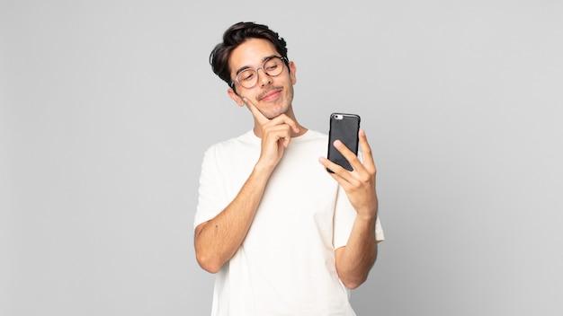 Junger hispanischer mann, der glücklich lächelt und träumt oder zweifelt und ein smartphone hält