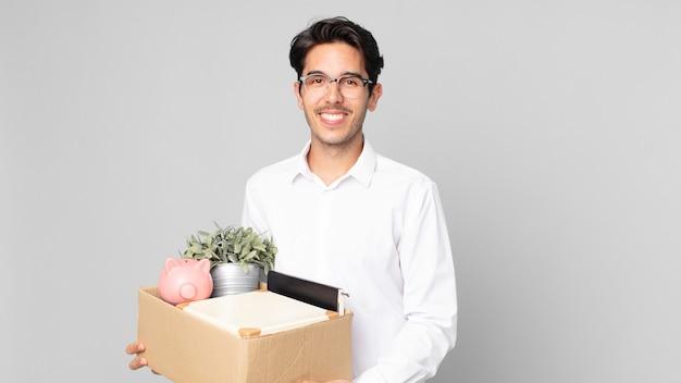 Junger hispanischer mann, der glücklich mit einer hand auf der hüfte und selbstbewusst lächelt. kündigungskonzept