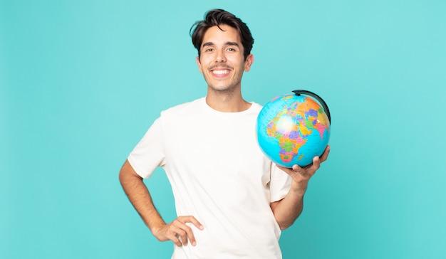 Junger hispanischer mann, der glücklich mit einer hand auf der hüfte und selbstbewusst lächelt und eine weltkugelkarte hält