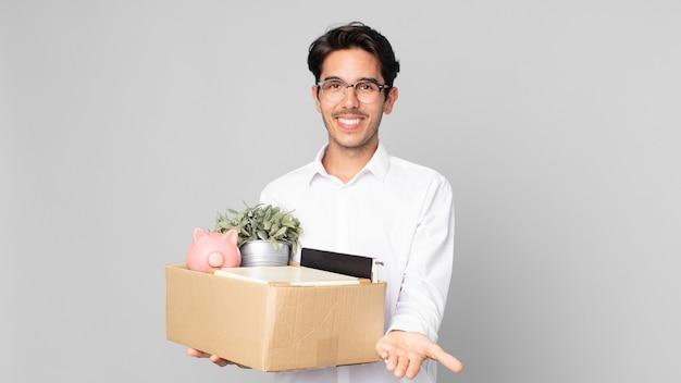 Junger hispanischer mann, der glücklich mit freundlichem lächeln lächelt und ein konzept anbietet und zeigt. kündigungskonzept