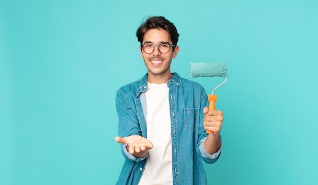 Junger hispanischer mann, der glücklich mit freundlichem lächeln lächelt und ein konzept anbietet und zeigt und einen farbroller hält