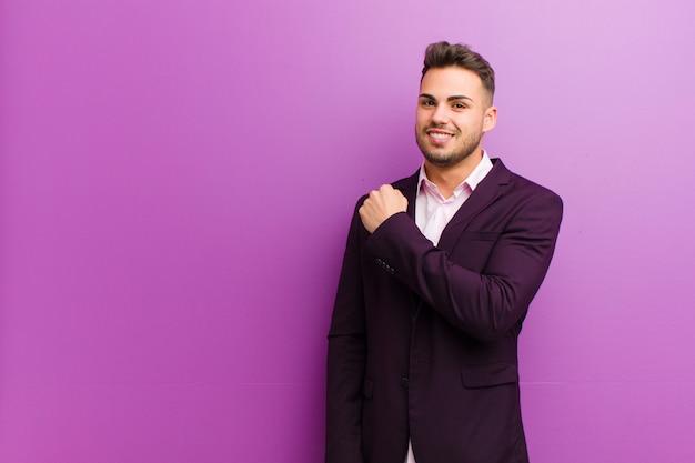 Junger hispanischer mann, der glücklich, positiv und erfolgreich sich fühlt, motiviert, wenn er einer herausforderung gegenübersteht oder gute ergebnisse feiert
