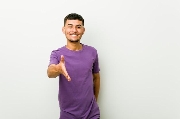 Junger hispanischer mann, der hand in der grußgeste ausdehnt.