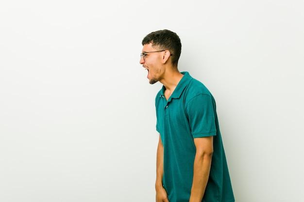 Junger hispanischer mann, der in richtung zu einem exemplarplatz schreit