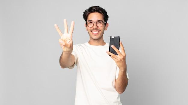 Junger hispanischer mann, der lächelt und freundlich aussieht, nummer drei zeigt und ein smartphone hält