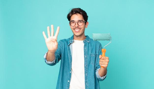 Junger hispanischer mann, der lächelt und freundlich aussieht, nummer vier zeigt und einen farbroller hält?