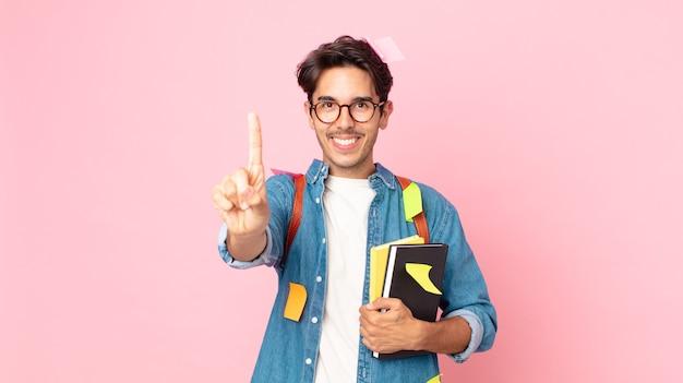 Junger hispanischer mann, der lächelt und freundlich aussieht und nummer eins zeigt. studentisches konzept