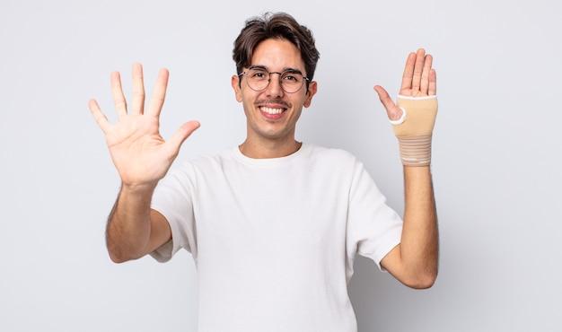 Junger hispanischer mann, der lächelt und freundlich aussieht und nummer fünf zeigt. handverbandkonzept
