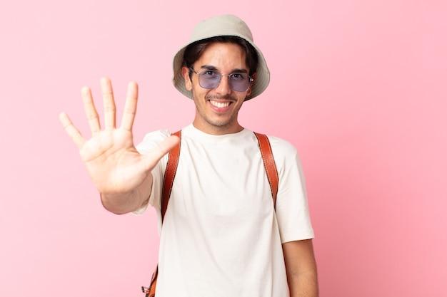 Junger hispanischer mann, der lächelt und freundlich aussieht und nummer fünf zeigt. sommerkonzept