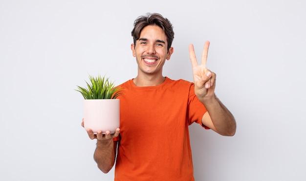Junger hispanischer mann, der lächelt und freundlich aussieht und nummer zwei zeigt. dekoratives pflanzenkonzept