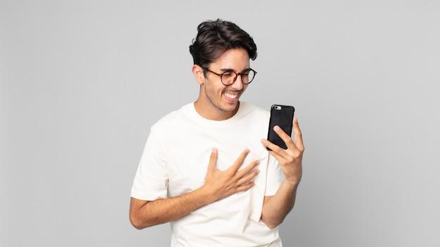 Junger hispanischer mann, der laut über einen lustigen witz lacht und ein smartphone hält