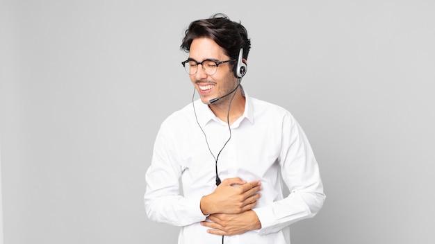 Junger hispanischer mann, der laut über einen urkomischen witz lacht. telemarketing-konzept