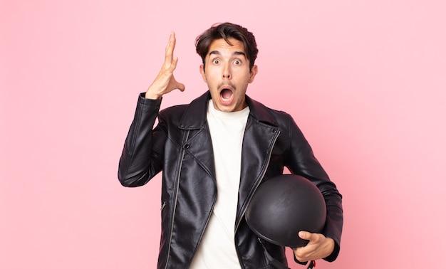 Junger hispanischer mann, der mit den händen in die luft schreit. motorradfahrerkonzept