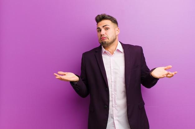 Junger hispanischer mann, der mit einem dummen, verrückten, verwirrten, verwirrten ausdruck die achseln zuckt und sich genervt und ahnungslos fühlt