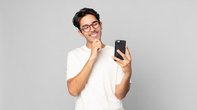 Junger hispanischer mann, der mit einem glücklichen, selbstbewussten ausdruck mit der hand am kinn lächelt und ein smartphone hält