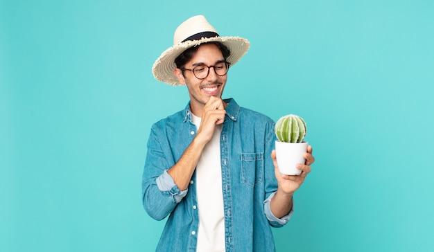 Junger hispanischer mann, der mit einem glücklichen, selbstbewussten ausdruck mit der hand am kinn lächelt und einen kaktus hält